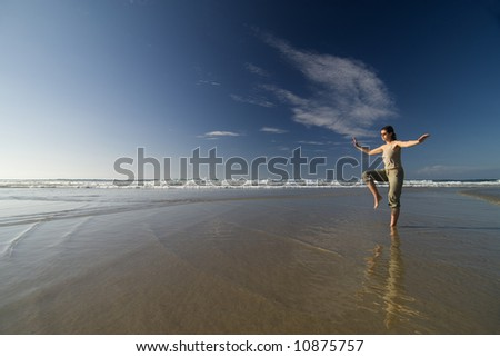 woman doing tai chi by the seashore in a sunny day - stock photo