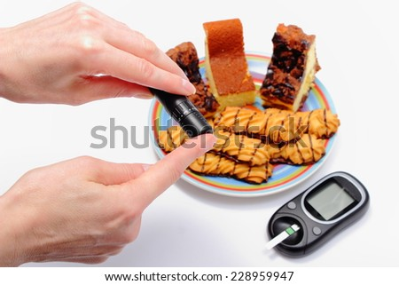 Woman doing test for determination level sugar, glucose meter and fresh baked pastry on colorful plate in background, concept for diabetes and glucose level test - stock photo