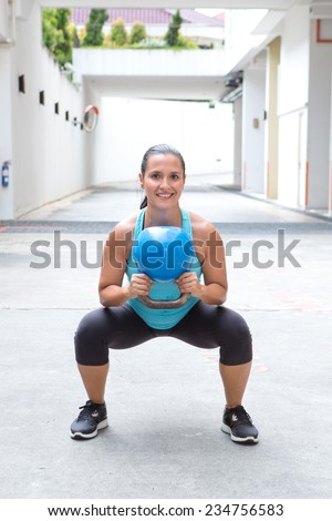 Woman doing the kettlebell squat for muscle strengthening exercise, outdoors - stock photo
