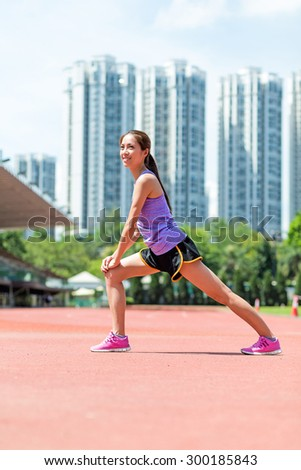 Woman doing warm up exercise in sport stadium - stock photo