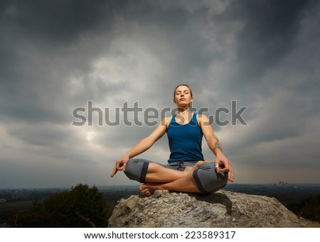 Woman doing yoga against the setting sun. Fitness classes outdoors. Stormy sky with sunshine. Attractive fitness woman, trained female body, lifestyle portrait, caucasian model - stock photo
