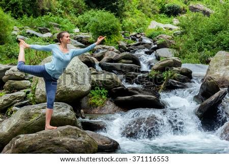 Woman doing yoga asana Natarajasana - Lord of the dance pose outdoors at waterfall in Himalayas - stock photo