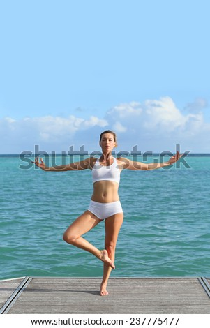 Woman doing yoga exercises by the sea - stock photo