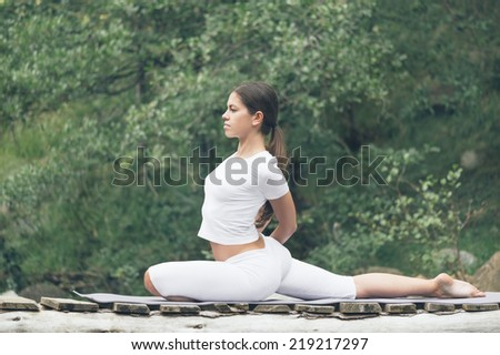 Woman doing yoga in nature. - stock photo
