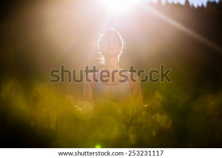 Woman doing yoga in sunset, backlit situation - stock photo