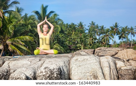 Woman doing yoga lotus pose on the stone at blue sky and tropical background in Kovalam, Kerala, India - stock photo