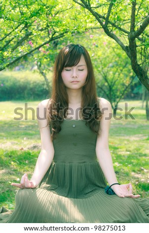 woman doing yoga meditation in outdoor park setting,green background - stock photo