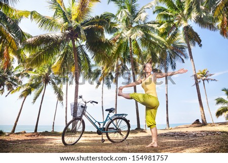 Woman doing yoga near bicycle with basket on the beach near palm trees and ocean in India - stock photo