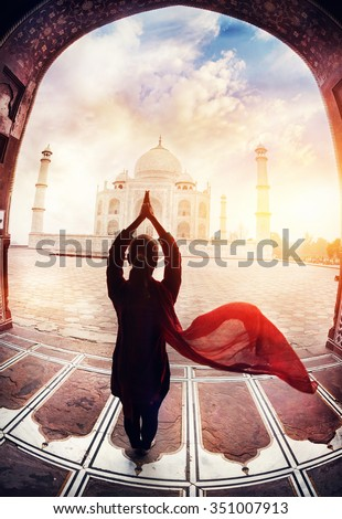 Woman doing yoga tadasana tree pose with flying red scarf in silhouette near Taj Mahal in Agra, Uttar Pradesh, India - stock photo