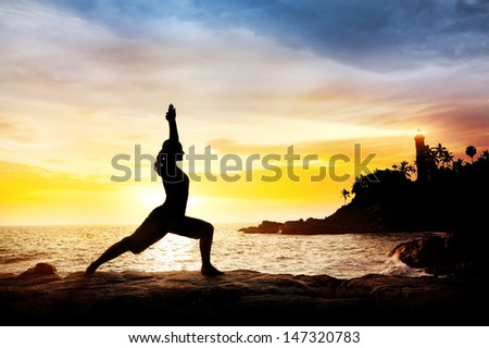 Woman doing Yoga warrior pose in silhouette on the cliff near lighthouse at sunset sky in Kovalam, Kerala, India - stock photo