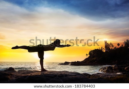 Woman doing Yoga warrior pose in silhouette on the stones near lighthouse at sunset sky in Kovalam, Kerala, India - stock photo