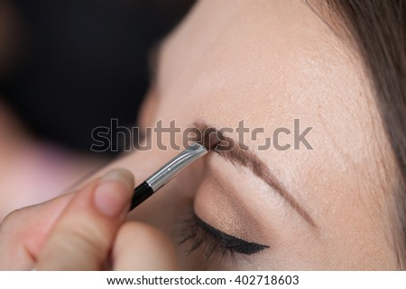 Woman drawing eyebrows on a client with a brush. - stock photo
