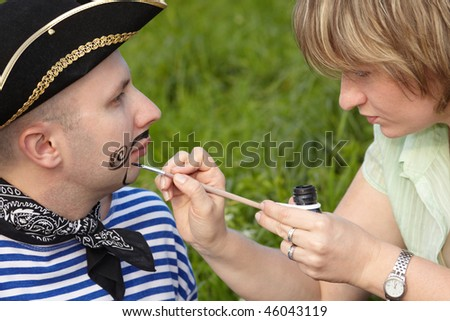 woman drawing funny whiskers and beard on man's face - stock photo