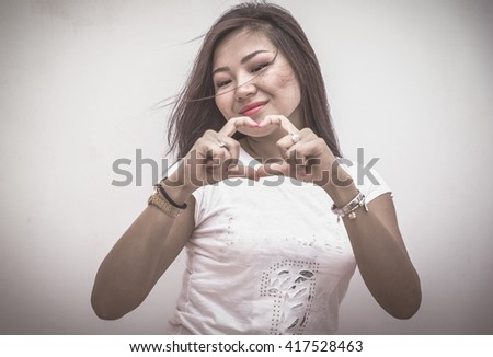Woman drawing heart with hands. Dramatic portrait image taken in studio. Asian happy girl with white background - stock photo