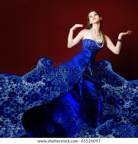 Woman dressed in blue soap bubble evening garment, grain added - stock photo