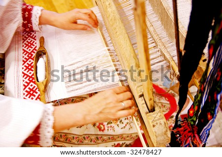 Woman dressed in folk clothing weaves a towel with a shuttle at the ancient Russian wooden loom at a folk festival - stock photo
