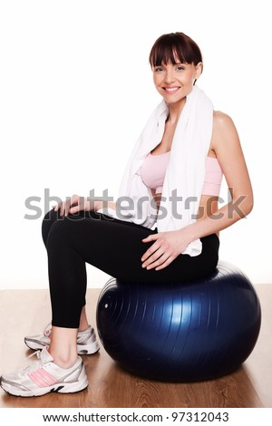 Woman dressed in sportswear with a towel round her shoulders sitting on a pilates ball - stock photo