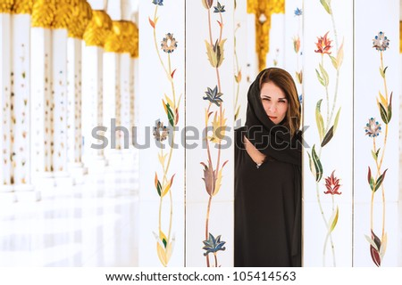 woman dressed in traditional Arab mosque near columns - stock photo