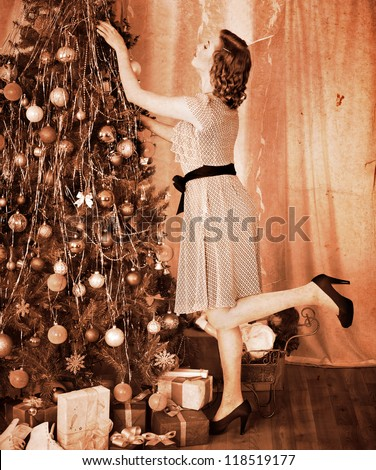 Woman dressing Christmas tree. Black and white. - stock photo