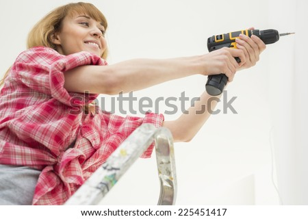 Woman drilling wall in new house - stock photo