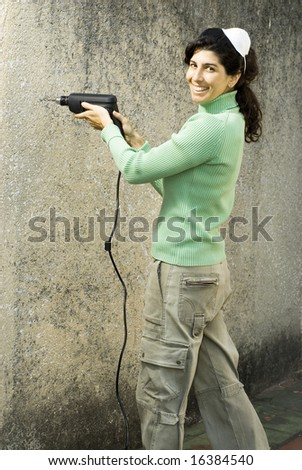 Woman drills hole in wall. She is smiling and wearing a dust mask on her head. Vertically framed photo. - stock photo