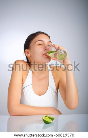 Woman drinking a glass of water with limes - stock photo