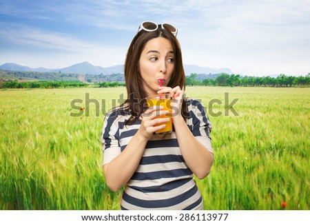 Woman drinking a juice with a red straw. Over meadow background - stock photo