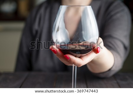 woman drinking alcohol on dark background. Focus on wine glass - stock photo