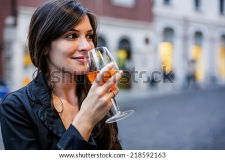 Woman drinking an aperitif in a bar - stock photo