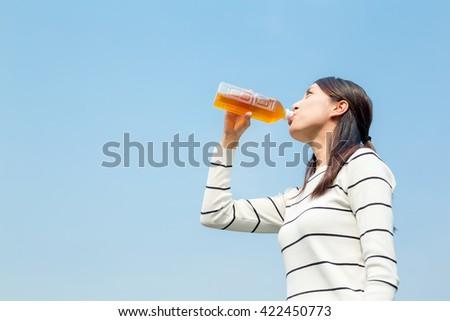 Woman drinking bottle of tea - stock photo