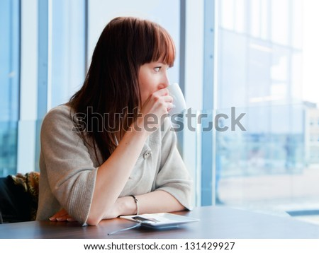 Woman drinking coffee at a corporate restaurant and looking at the window - stock photo