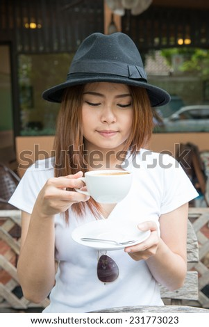 woman drinking coffee  at coffee shop (soft focus on eyes) - stock photo