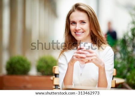 Woman drinking coffee at street cafe. Natural light - stock photo
