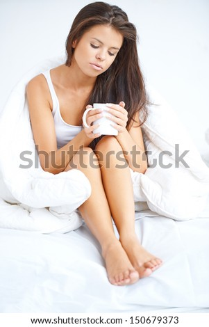 Woman drinking coffee in bed sitting in her pyjamas holding the mug cupped in her hands with a thoughtful downcast expression - stock photo