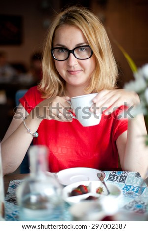 woman drinking coffee in the morning at restaurant , wearing eyeglasses  - stock photo