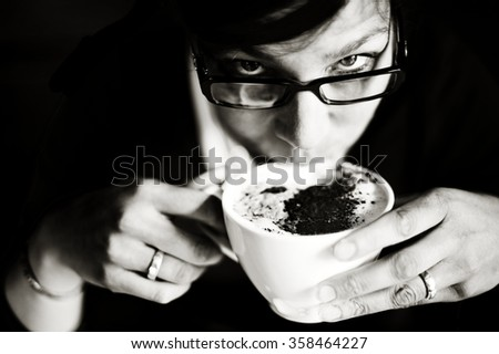 Woman drinking coffee - Monochrome image of woman enjoying a hot cup of coffee. - stock photo
