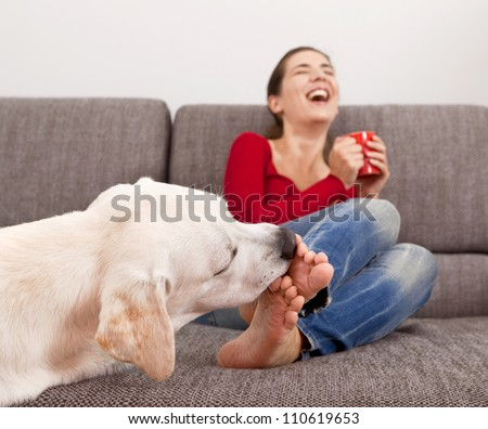 Woman drinking coffee on the sofa with her dog licking her toes - stock photo