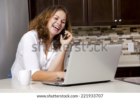 woman drinking coffee while chatting on the phone, using laptop - stock photo
