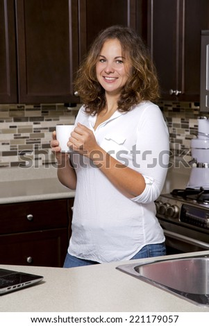 woman drinking coffee while working on the laptop in the kitchen - stock photo