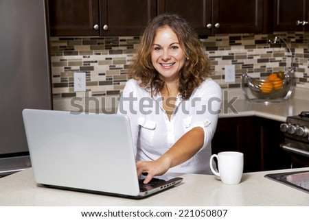woman drinking coffee while working on ther laptop in the kitchen - stock photo