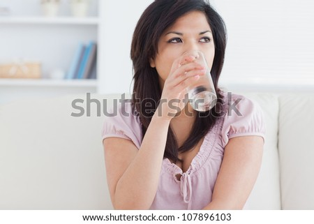 Woman drinking from a glass of water in a living room - stock photo