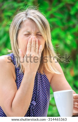 woman drinking her tea and sneezing due to allergic with green background - stock photo