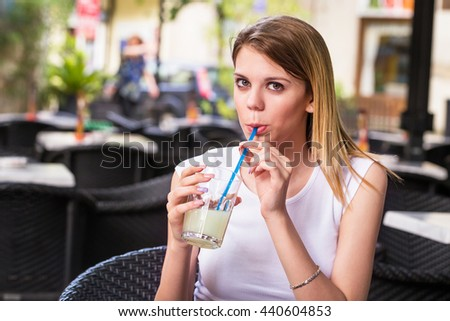 Woman drinking lemonade with a straw, in a restaurant - stock photo