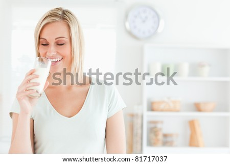 Woman drinking milk in kitchen - stock photo