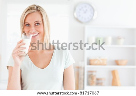 Woman drinking milk looks into camera in kitchen - stock photo