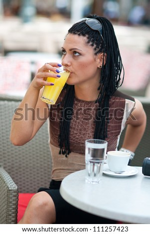 woman drinking orange juice in bar terrace - stock photo
