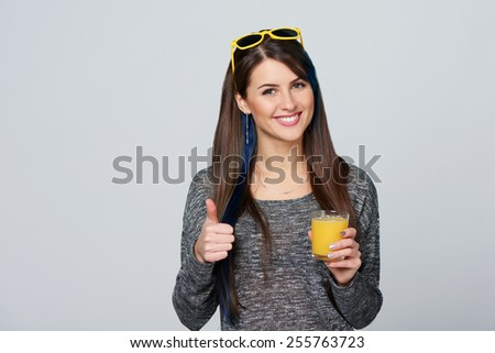 Woman drinking orange juice smiling showing thumb up, over gray background - stock photo