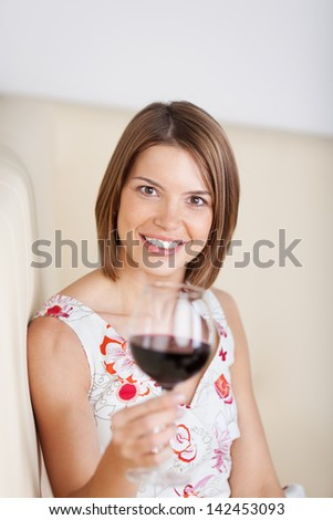 Woman drinking red wine in a restaurant holding up her glass to the camera with focus to her smiling face - stock photo
