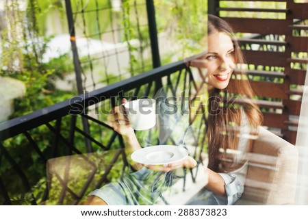 woman drinking tea at home. View through the window - stock photo