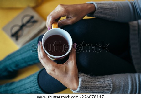 Woman drinking tea on the couch - stock photo